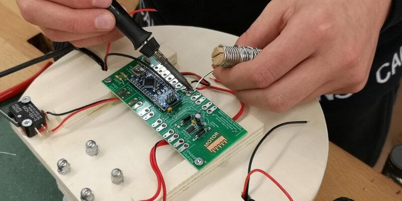 Schüler lötet Roboter